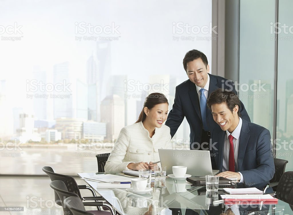 Business people using laptop in meeting stock photo