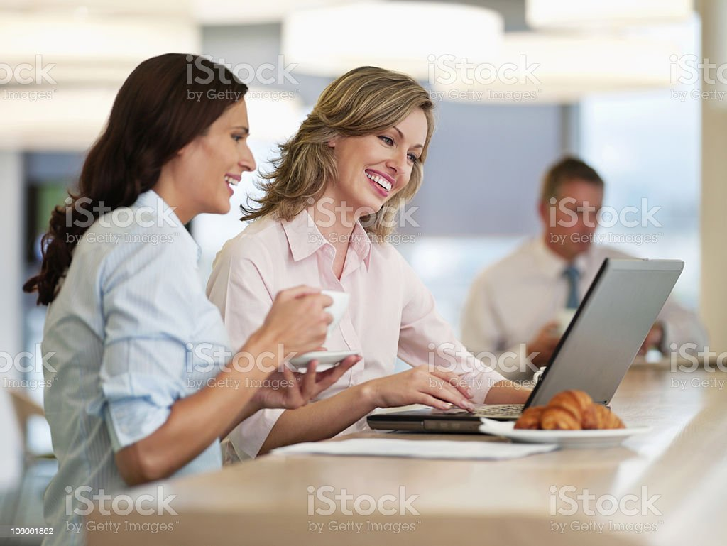 Business people using laptop with male colleague in the background royalty-free stock photo