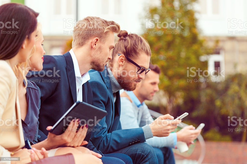 Business people using smart phone and digital tablet outdoor stock photo