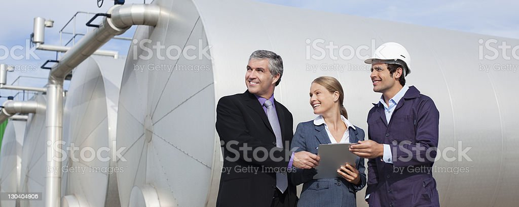 Business people using tablet computer by tanks royalty-free stock photo
