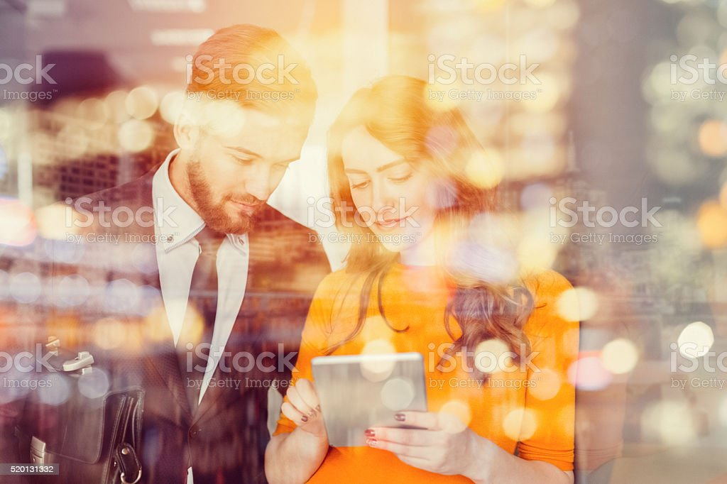Businessman and businesswoman surfing the net on digital tablet