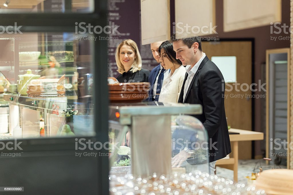 Business people waiting in line in cafeteria stock photo