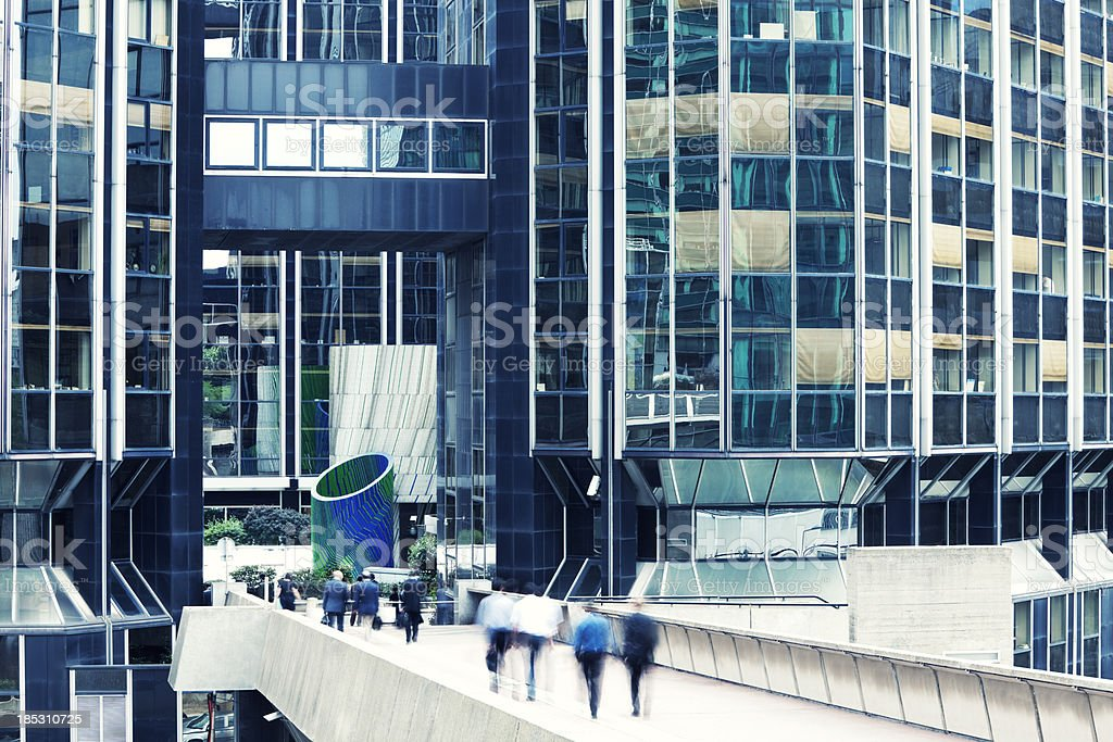 Business People Walking Across Footbridge to Office Building, Blurred Motion royalty-free stock photo