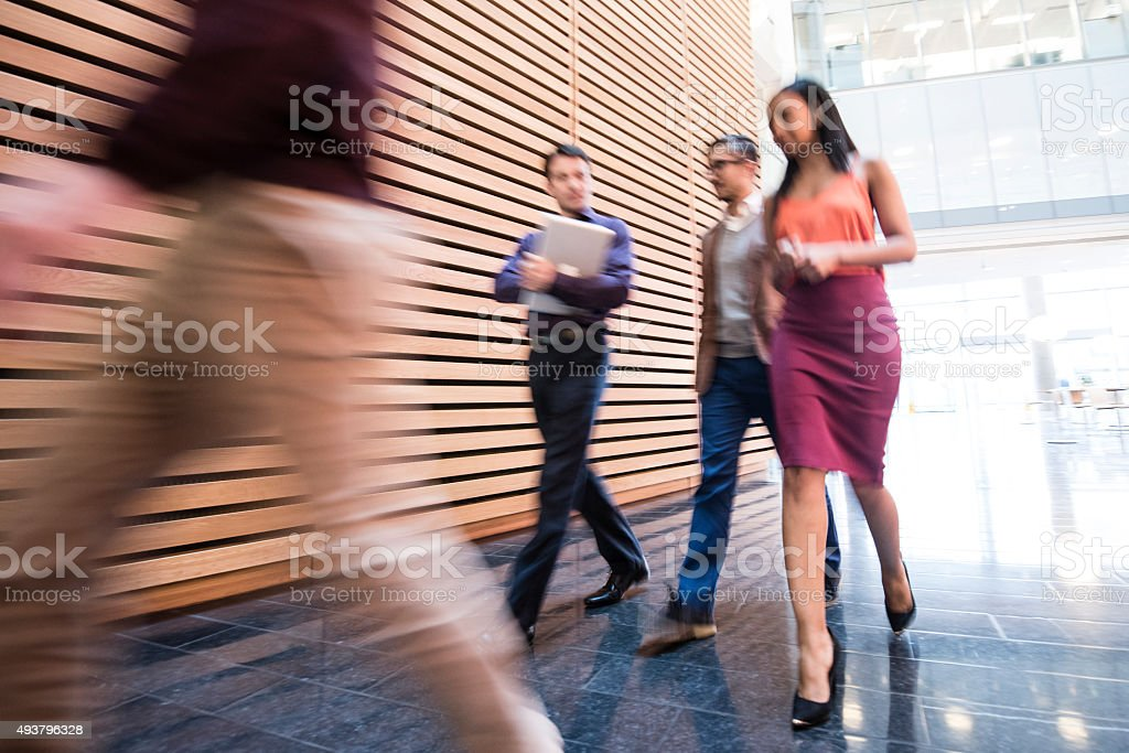 Business people walking in modern office with blurred motion stock photo