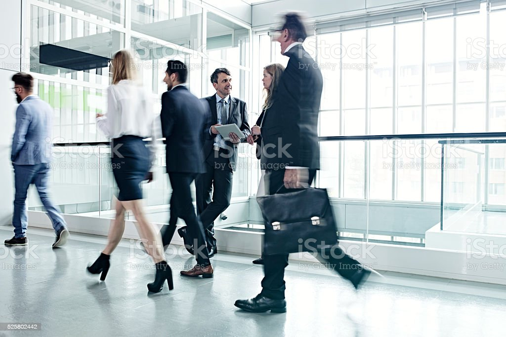 Business people walking in office lobby stock photo