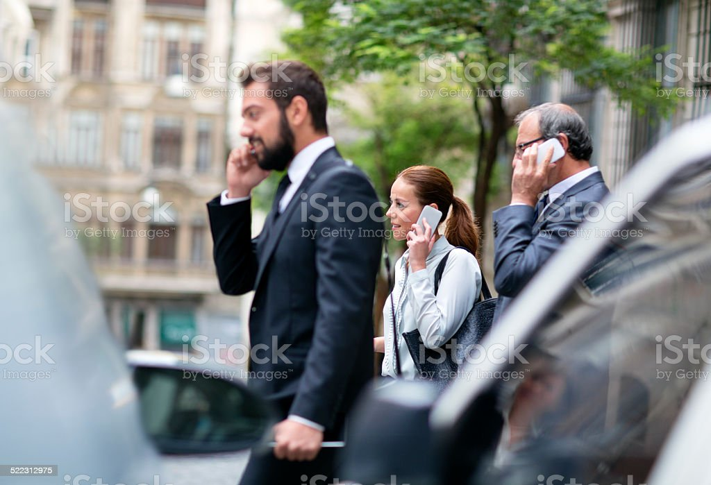 Business people walking in the city and using mobile phones stock photo