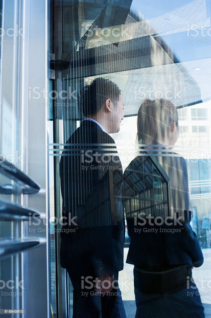 Business people walking out of glass door stock photo