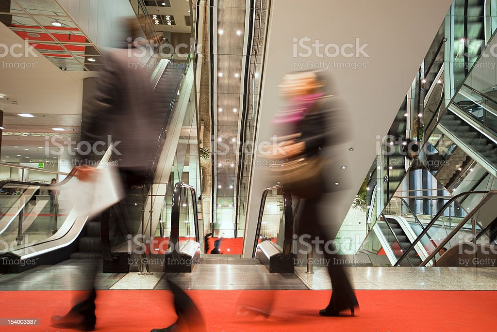 Business People Walking Red Carpet in Front of Escalators royalty-free stock photo