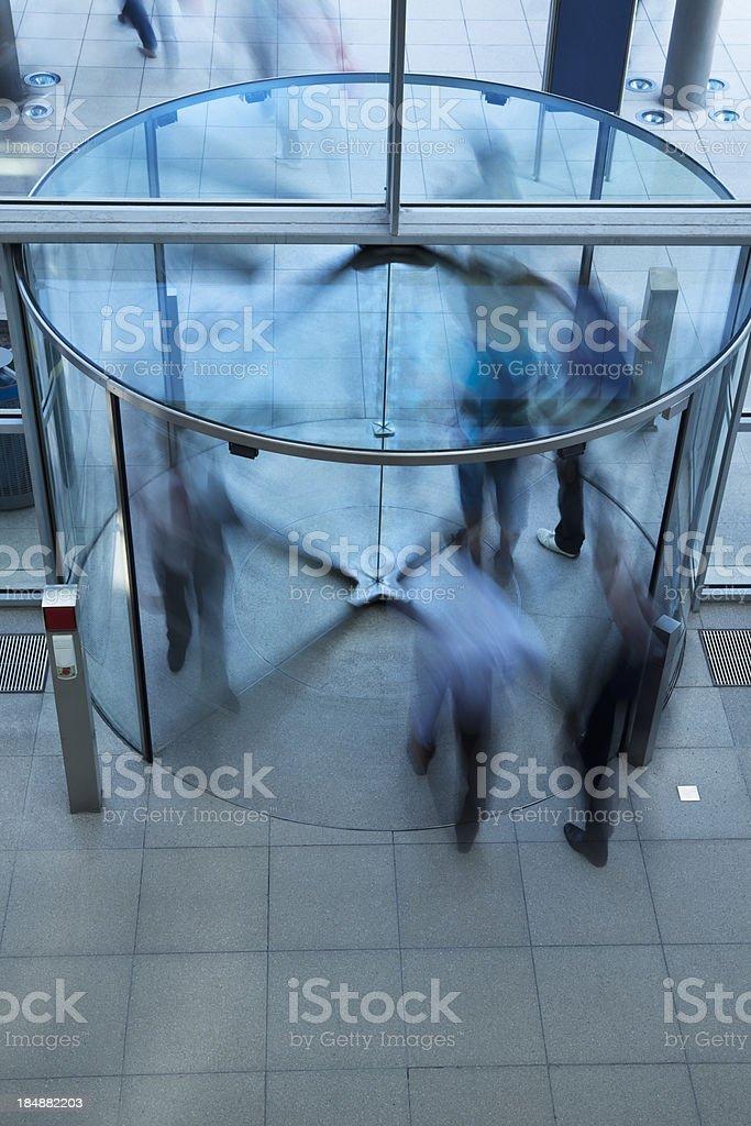 Business People Walking Through Glass Revolving Door stock photo
