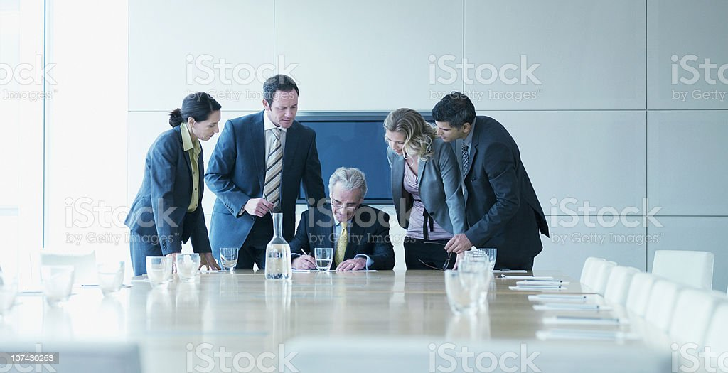 Business people watching boss sign contract stock photo