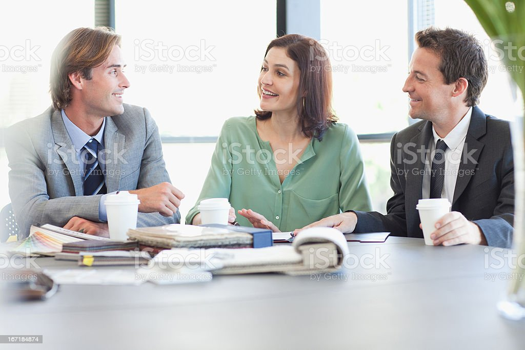 Business people with coffee talking at table in conference room royalty-free stock photo