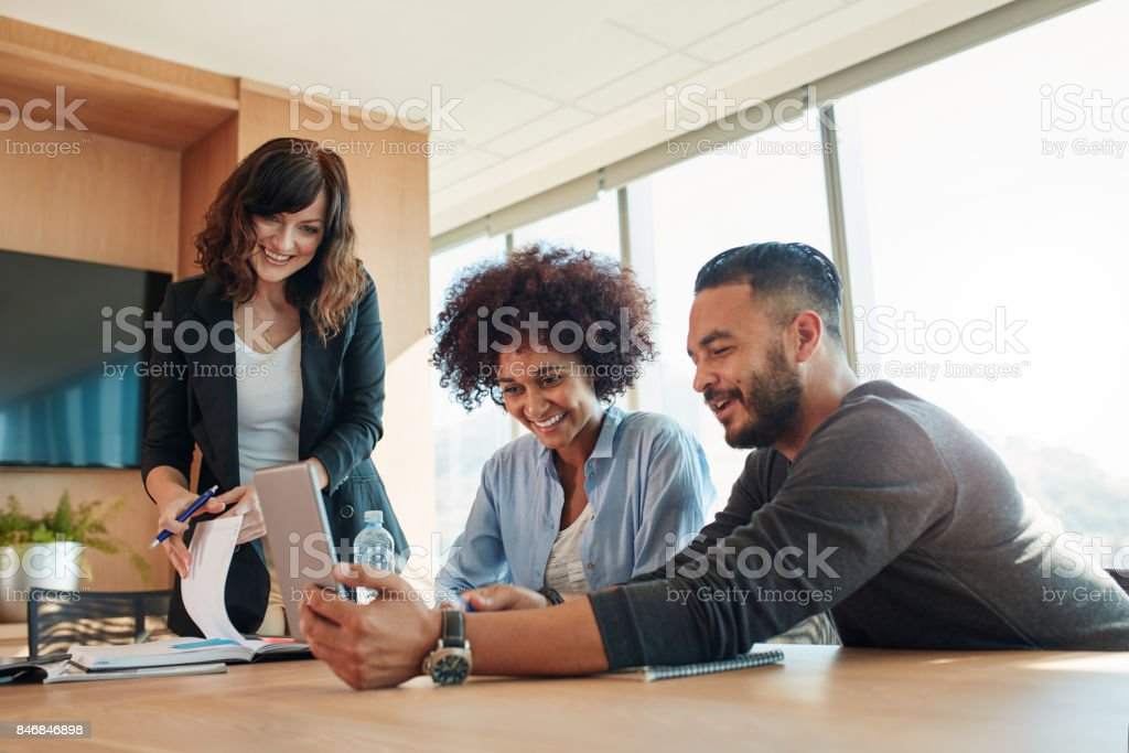Business people with digital tablet sitting in modern office stock photo