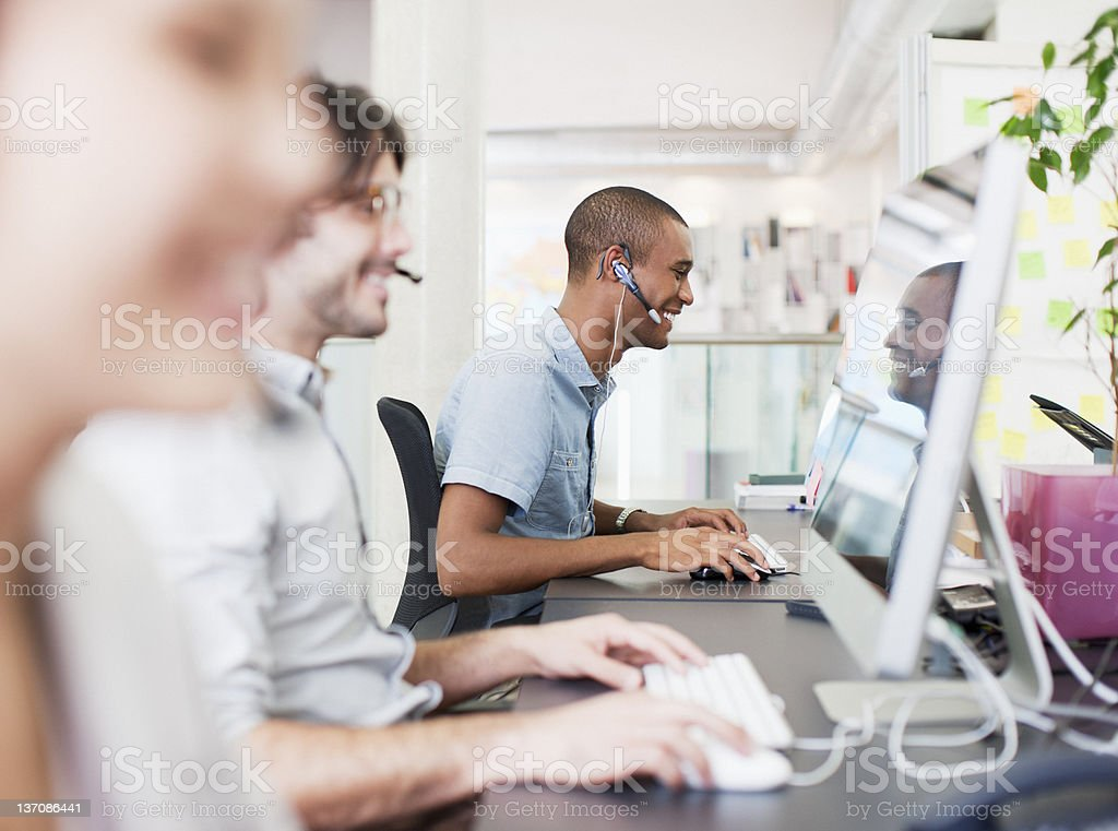 Business people with headsets working at computers in office stock photo