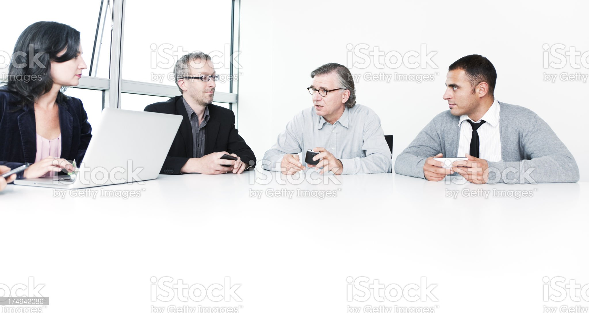 Business People with Laptop and Smart Phones at Conference Table royalty-free stock photo