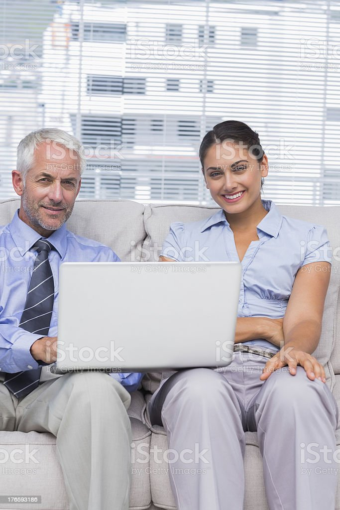 Business people with laptop smiling at camera sitting on couch royalty-free stock photo