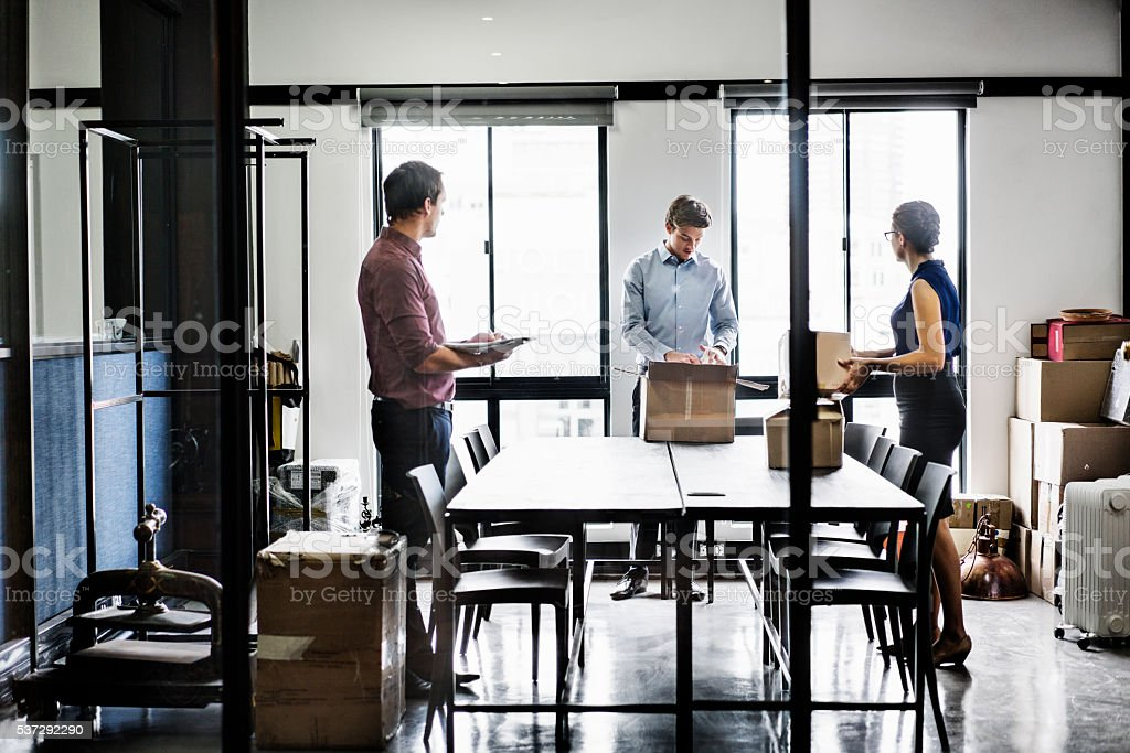 Business people with packing boxes in board room stock photo