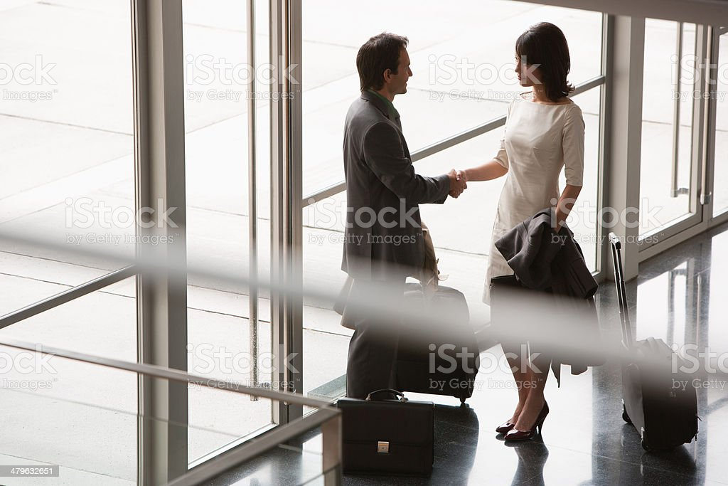 Business people with suitcases greeting one another stock photo