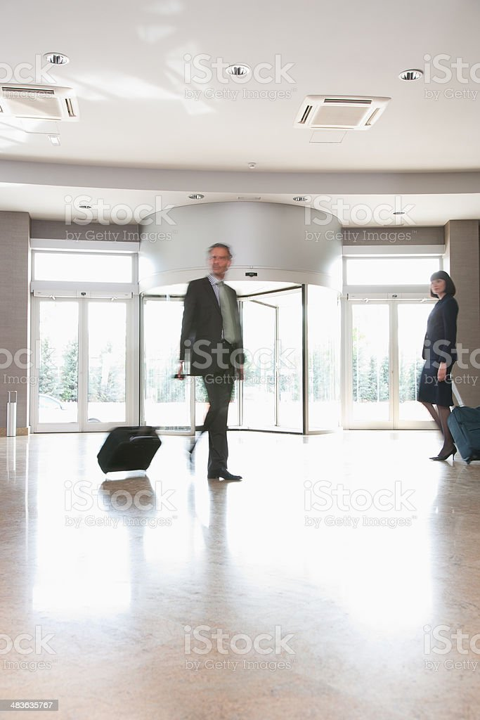 Business people with suitcases walking in lobby stock photo