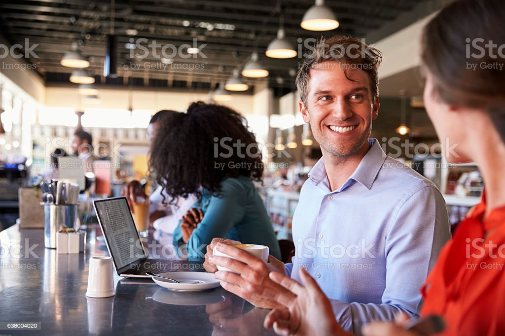 Business People Working At Counter In Coffee Shop stock photo