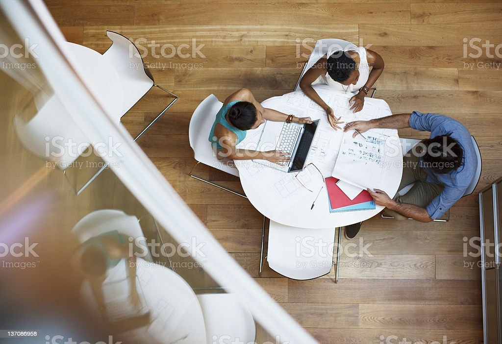 Business people working at table with laptop and paperwork stock photo