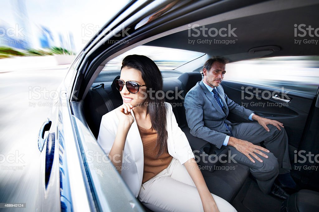 Business people working in backseat of car stock photo