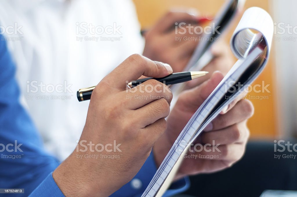 Business people writing on notepad stock photo