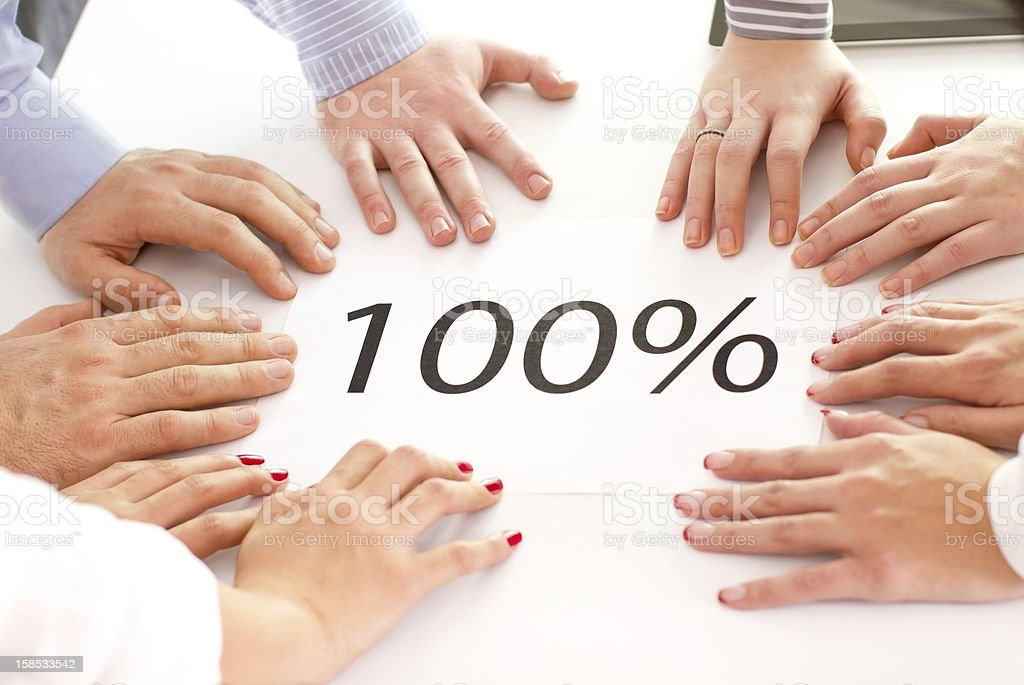 Business people's hands in a circle around a 100% on paper stock photo