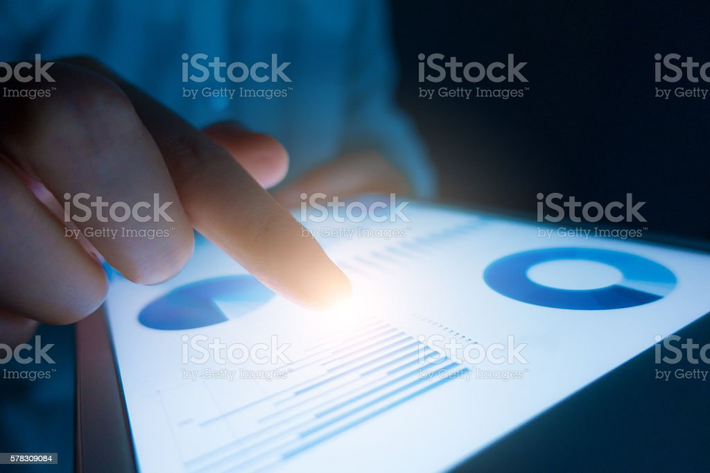 Business person analyzing financial statistics displayed on the tablet screen stock photo