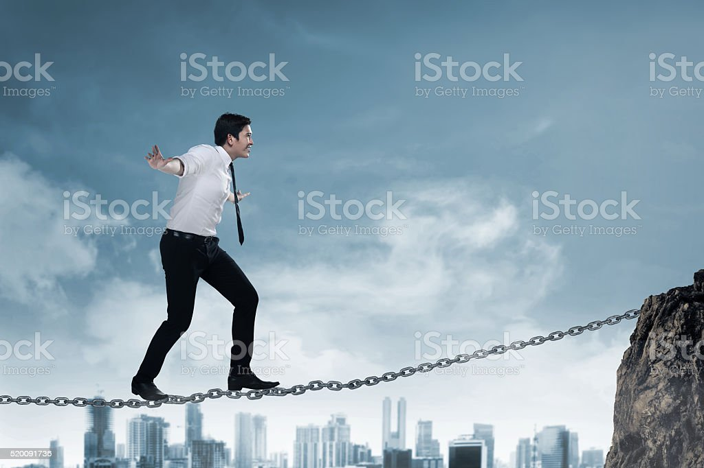 Business person balancing on the chain stock photo