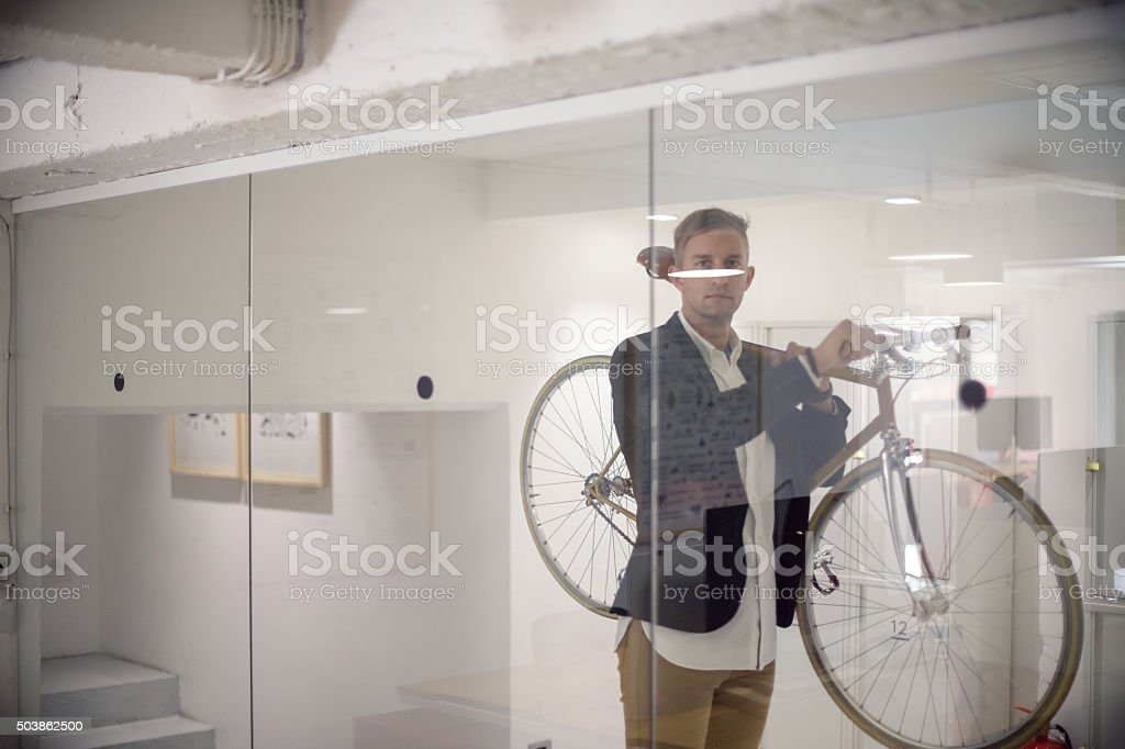 Business person carrying his bicycle stock photo