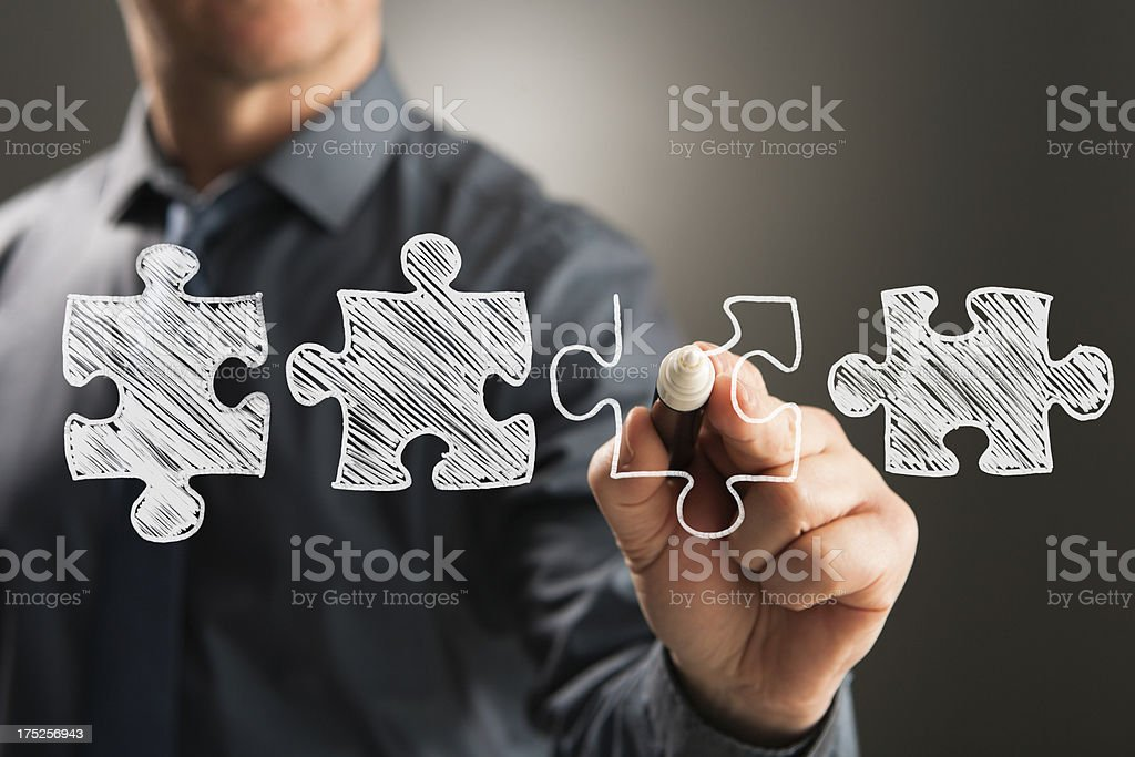 Business person drawing four jigsaw pieces stock photo