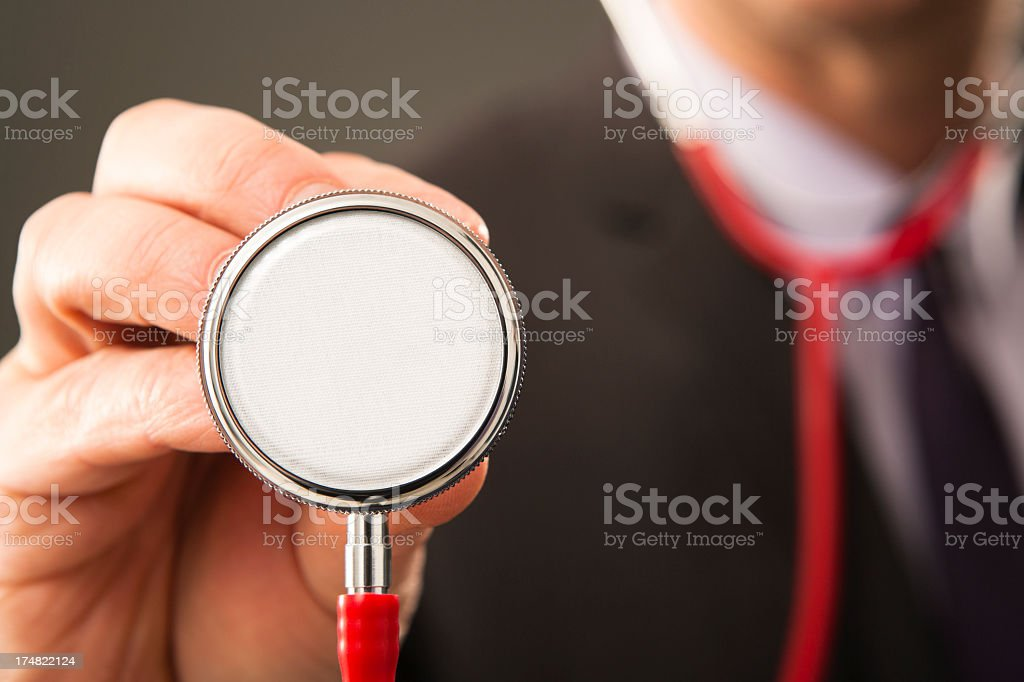 Business person examining with stethoscope stock photo