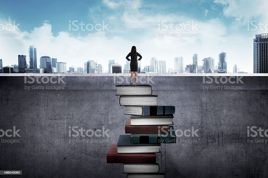 Business person looking the city standing on books stock photo