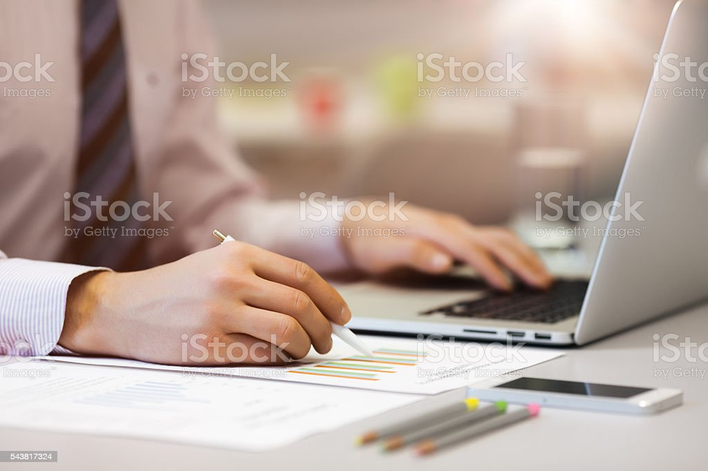 Business Person reading Data on paper Charts and Computer stock photo