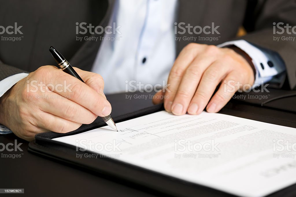 Business person signing a contract, focus on signature. stock photo