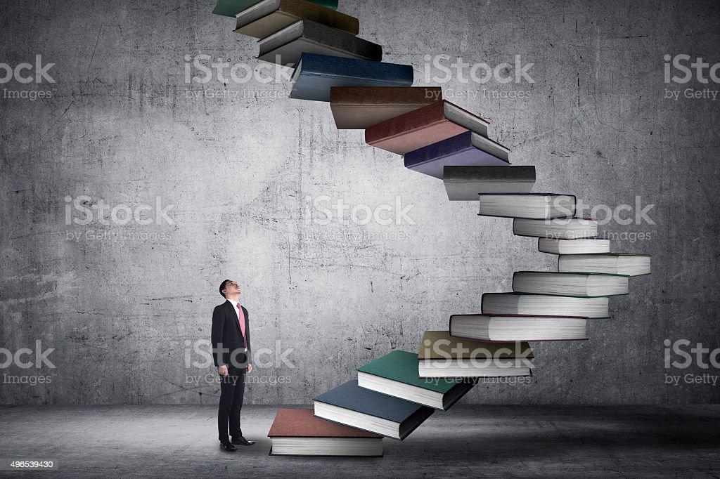 Business person step up flying book that look like stair stock photo