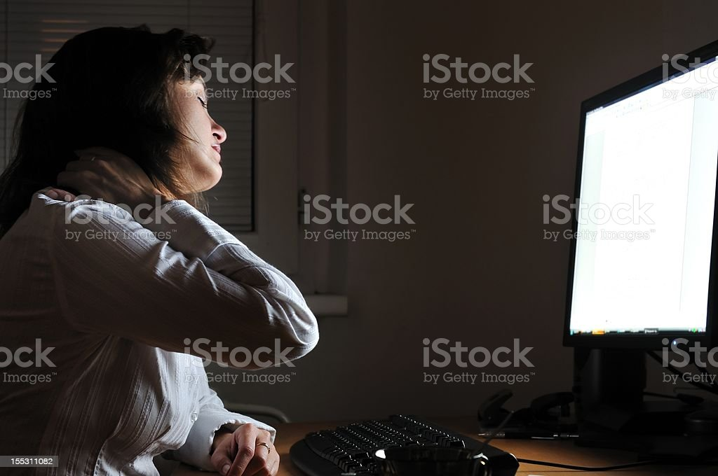 Business person working overtime with neck pain royalty-free stock photo