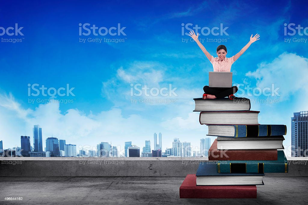 Business person working with laptop on  the top of books stock photo