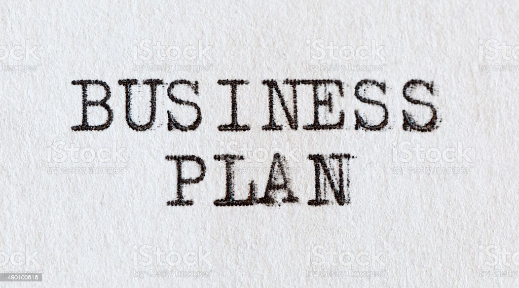Business plan written on white paper with old typewriter. stock photo