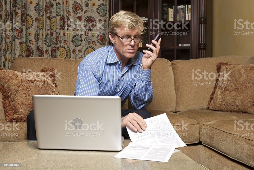 Business Pro Looks Over Contracts at Home stock photo