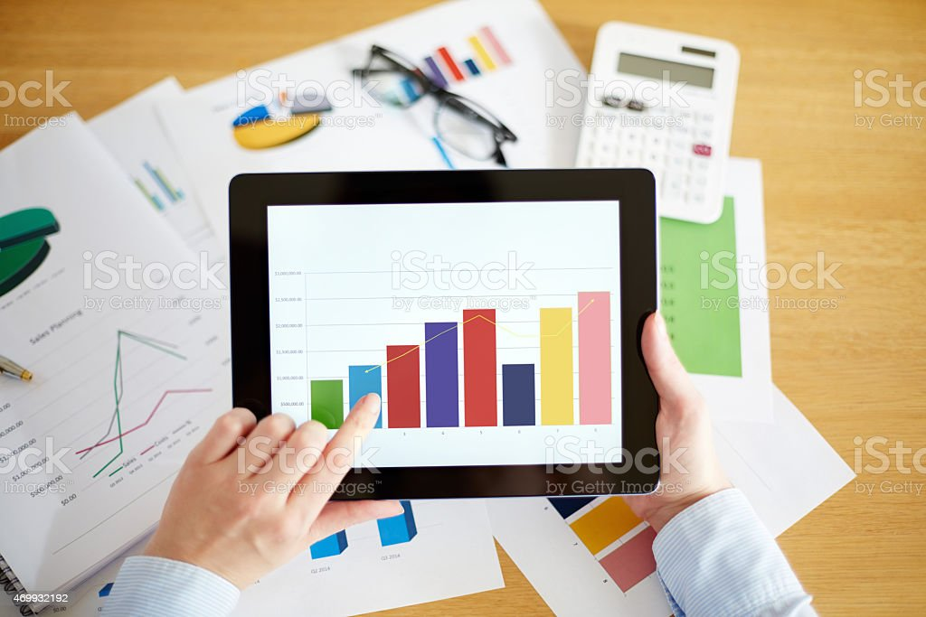 Business professional holding digital tablet showing sales graph stock photo