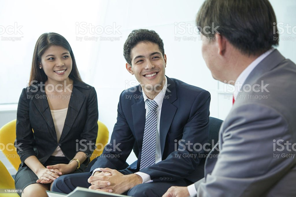 A business professional speaks to a young couple stock photo