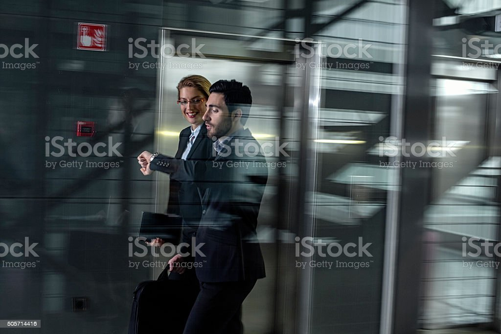 Business professionals passing through office building lobby stock photo