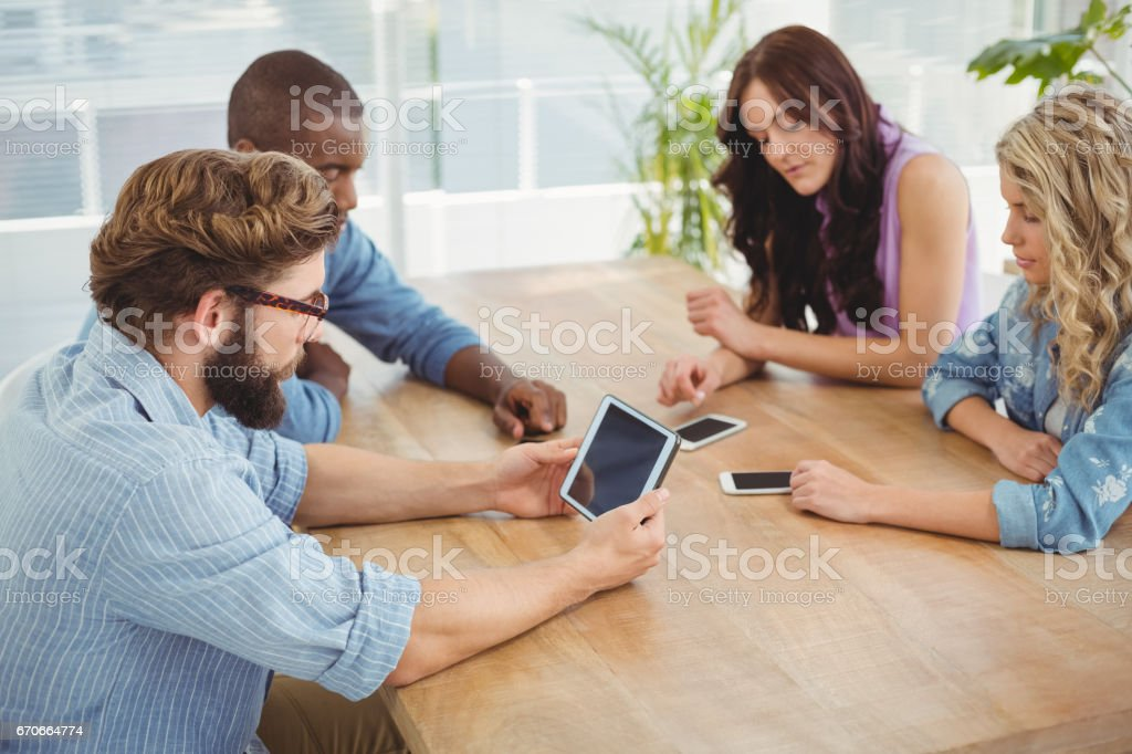 Business professionals using technology at desk stock photo