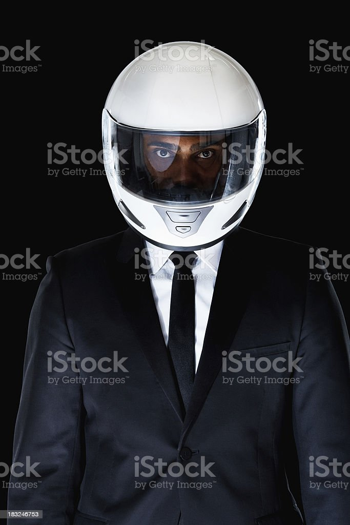 Business protection - Man wearing motorbike helmet against black royalty-free stock photo