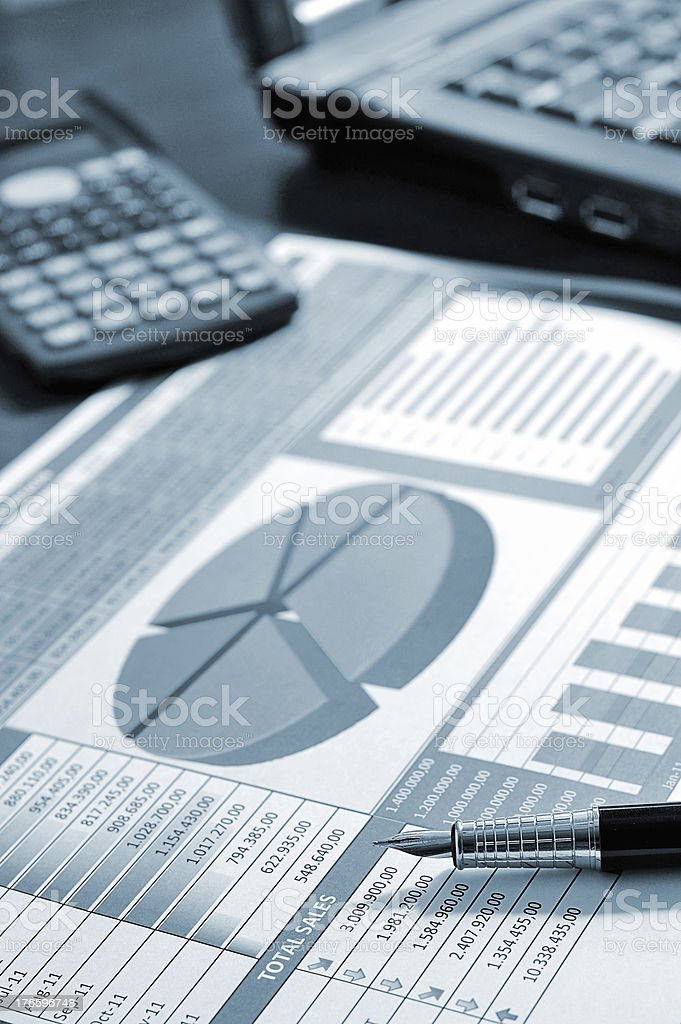 Business report next to a calculator and laptop stock photo
