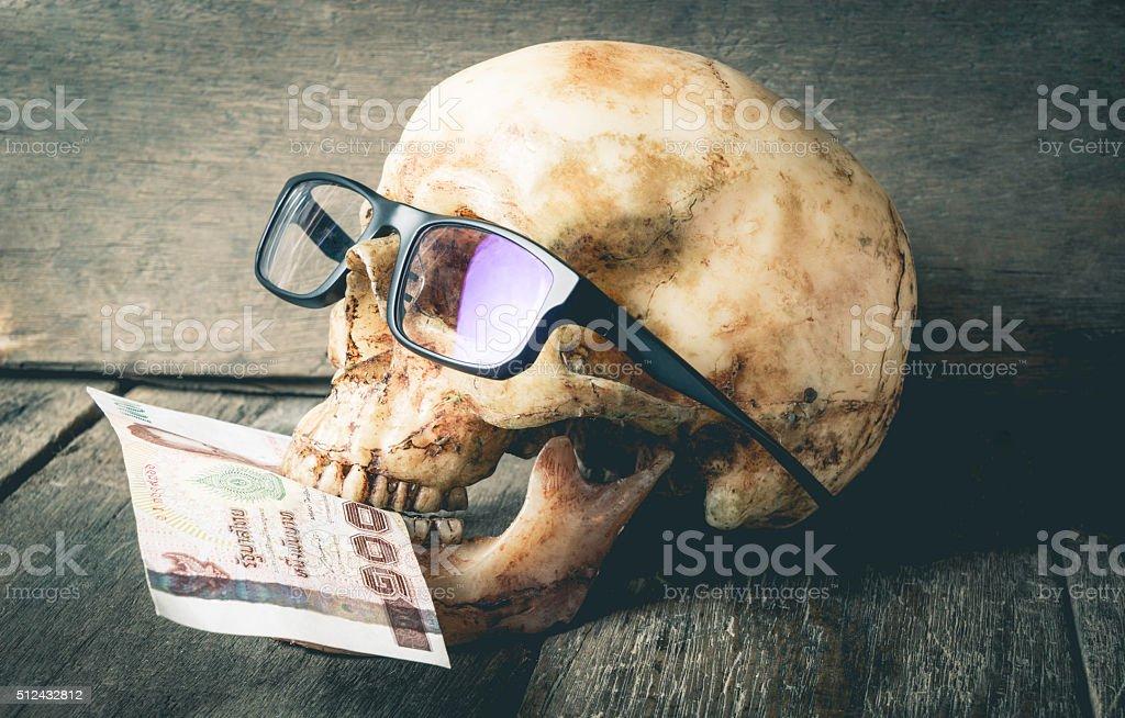 Business Skull is eating Thai Baht Note stock photo