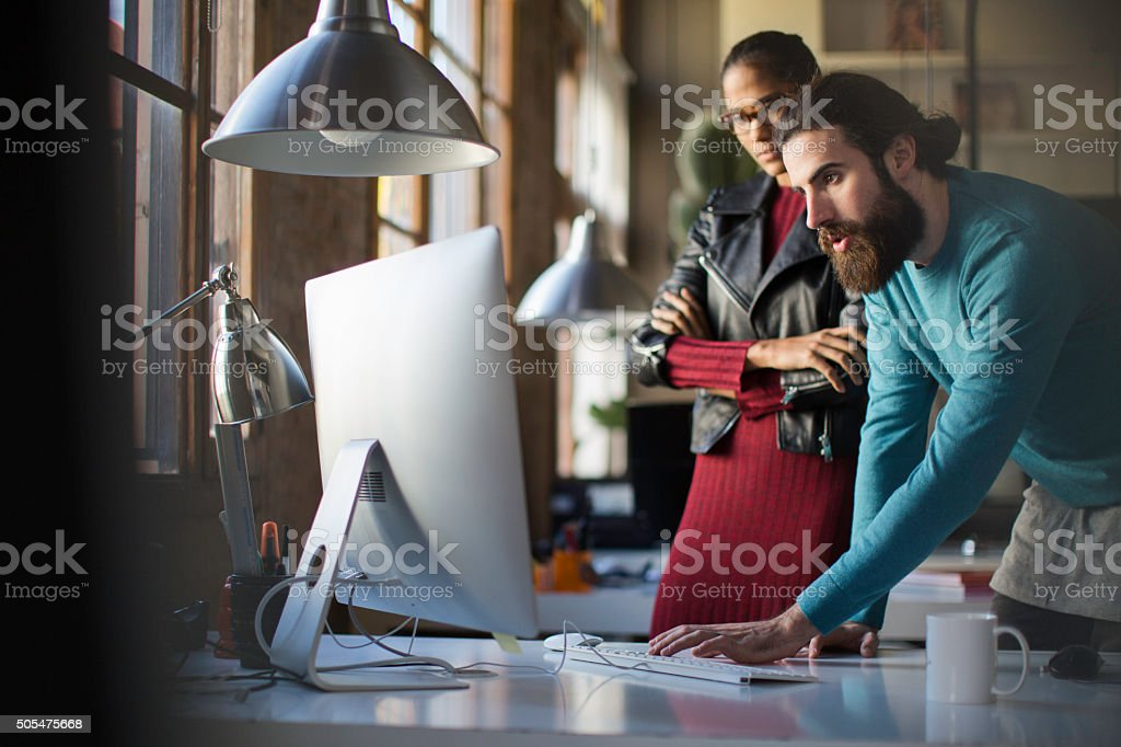 Business small meeting, two co-workers looking at computer. stock photo