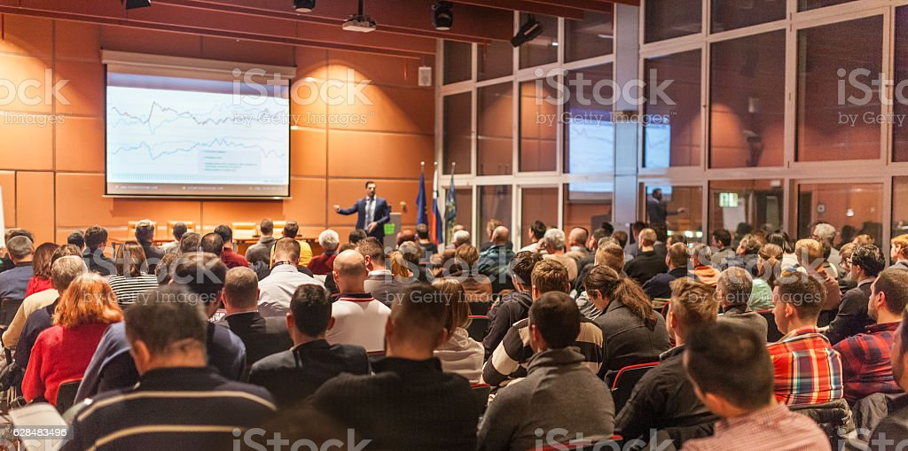 Business speaker giving a talk in conference hall. stock photo