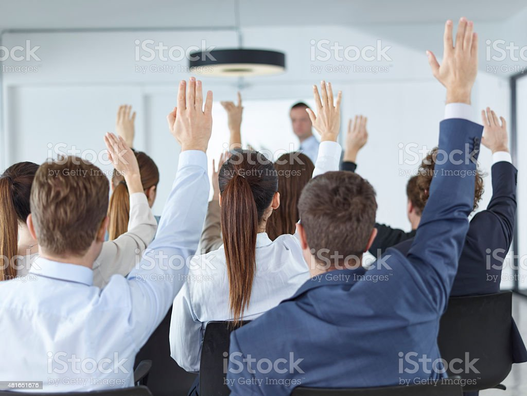Business Spectators Or Students Raising Hands In Seminar stock photo